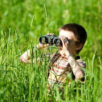 5111490-giovane-ragazzo-in-un-campo-guardando-attraverso-un-binocolo